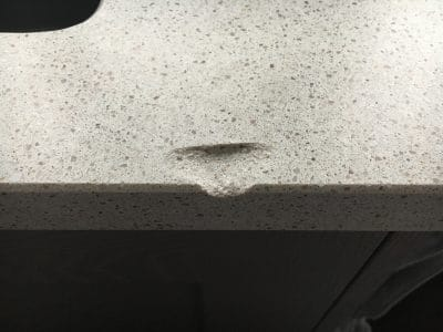 Engineered Quartz Kitchen Worktop Edge Chip Repair | Close up of the damaged edge