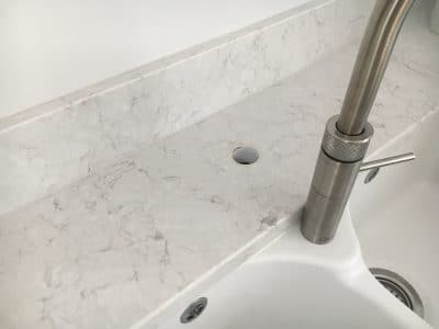Engineered Quartz Stone Worktop Tap Hole Repair | The original hole can be seen behind the new location of the tap