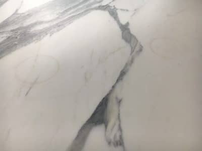 Marble Table Red Wine Stain Removal Repair | Close up of the surface shows obvious bottle ring marks