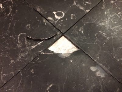 Black Marble Floor Tile With Broken Corner Repaired | Broken 4cm sq marble piece is out for cleaning and resin repairs.