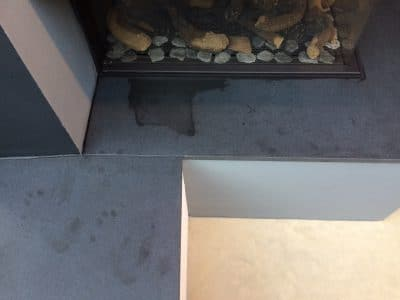 Granite Fireplace Oil Wax Stain Removal | Over view of the stain and finger prints near by.