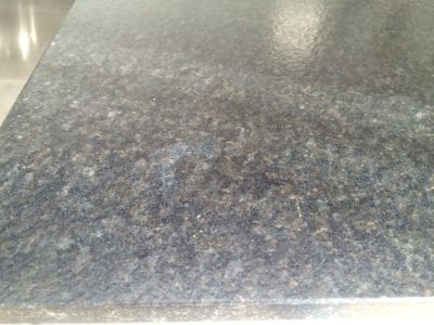 Granite Kitchen Surface Stain Clean St Edwards | Close up of textured granite and staining.