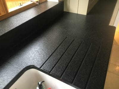 Kitchen Black Granite Surfaces Clean And Treatment | After the cleaning and treatment the work top and draining grooves look uniform in colour with no stains.