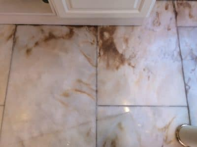 Marble Floor Humidity Stain Removal | Brown contamination stains are very obvious near cupboard.