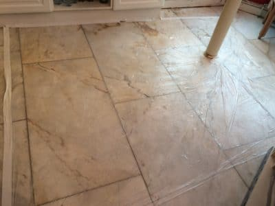 Marble Floor Humidity Stain Removal | The floor is being treated and covered with plastic sheets.