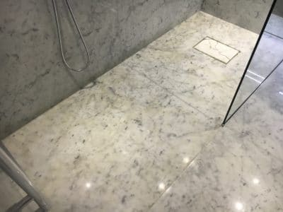Marble Shower Humidity Contamination Stain Removal | Over view of shower floor and wall tiles showing stains all over the floor and waved line on wall tiles.