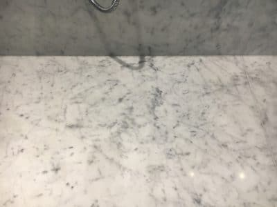 Marble Shower Humidity Contamination Stain Removal | Close up of stain-free floor tiles after cleaning.