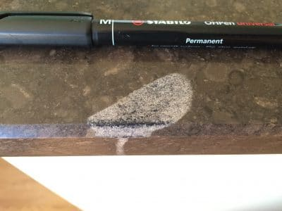 Quartz Kitchen Top Acid Stain Removal | Close up near pen scale.