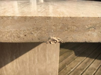 Travertine Stone Table Damage From Fallen Roof Tiles | Edge repairs in progress.