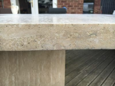 Travertine Stone Table Damage From Fallen Roof Tiles | Edge repaired and polished (close up view)