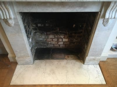 White Marble Fireplace Stain Removal | Overview of fireplace before the cleaning.